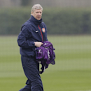 Arsenal's manager Arsene Wenger carries bibs during a training session at their London Colney training ground, Monday, March 10, 2014. Arsenal will play in a Champions League last sixteen second leg soccer match against Munich in Germany on Tuesday