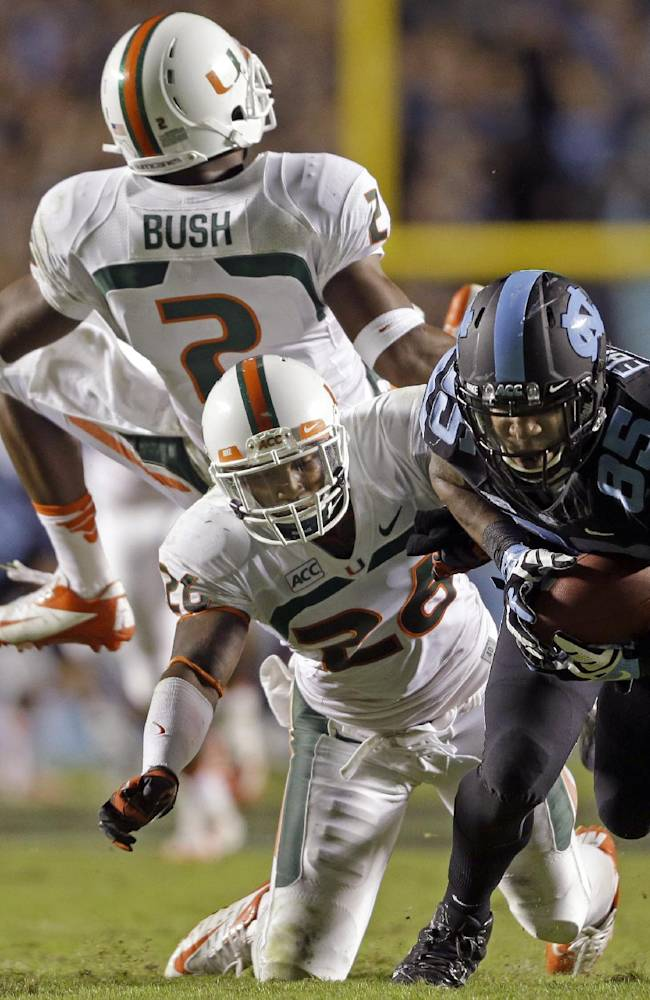 North Carolina's Eric Ebron (85) gains some yardage following a pass reception as Miami's Deon Bush (2) and  Rayshawn Jenkins defend during the first half of an NCAA college football game in Chapel Hill, N.C., Thursday, Oct. 17, 2013