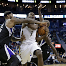 New Orleans Pelicans forward Tyreke Evans (1) is fouled as he drives to the basket between Sacramento Kings center DeMarcus Cousins, right, and forward Quincy Acy in the second half of an NBA basketball game in New Orleans, Monday, March 31, 2014. The Kin