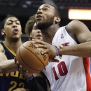 Detroit Pistons center Greg Monroe (10) is fouled on the wrist by New Orleans Hornets guard Brian Roberts, left, while going to the basket in the first half of an NBA basketball game, Monday, Feb. 11, 2013, in Auburn Hills, Mich. (AP Photo/Duane Burleson)