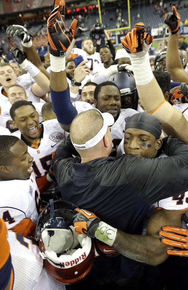Syracuse coach Scott Shafer, center left, hugs running back Jerome Smith, center right, as they celebrate with their team after winning the Texas Bowl NCAA college football game against Minnesota, Friday, Dec. 27, 2013, in Houston. Syracuse won 21-17
