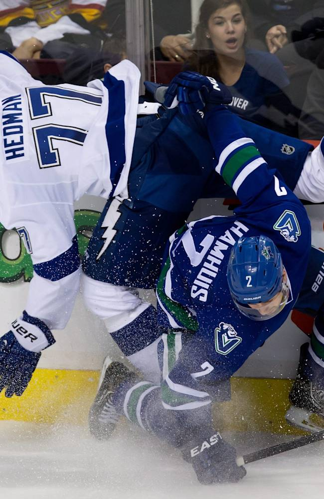 Vancouver Canucks' Dan Hamhuis, bottom, checks Tampa Bay Lightning's Victor Hedman, of Sweden, during the second period of an NHL hockey game Wednesday, Jan. 1, 2014, in Vancouver, British Columbia