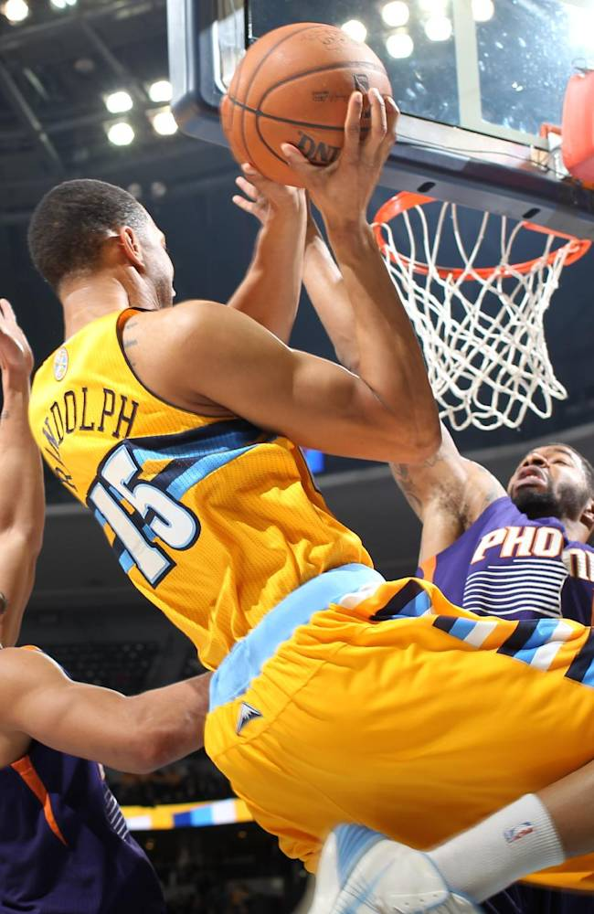 Denver Nuggets forward Anthony Randolph, center, drives for a shot as Phoenix Suns guard Gerald Green, left, and forward Markieff Morris cover in the fourth quarter of the Suns' 103-99 victory in an NBA basketball game in Denver on Friday, Dec. 20, 2013