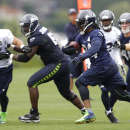 Seattle Seahawks running back Marshawn Lynch, third from left, carries the ball on the final day of NFL football training camp, Wednesday, Aug. 13, 2014, in Renton, Wash The Associated Press