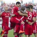 Toronto FC 's Justin Morrow (2) is mobbed by teammates after scoring his team's opening goal against the Chicago Fire during the first half of a soccer game, Saturday, Aug. 23, 2014 in Toronto The Associated Press