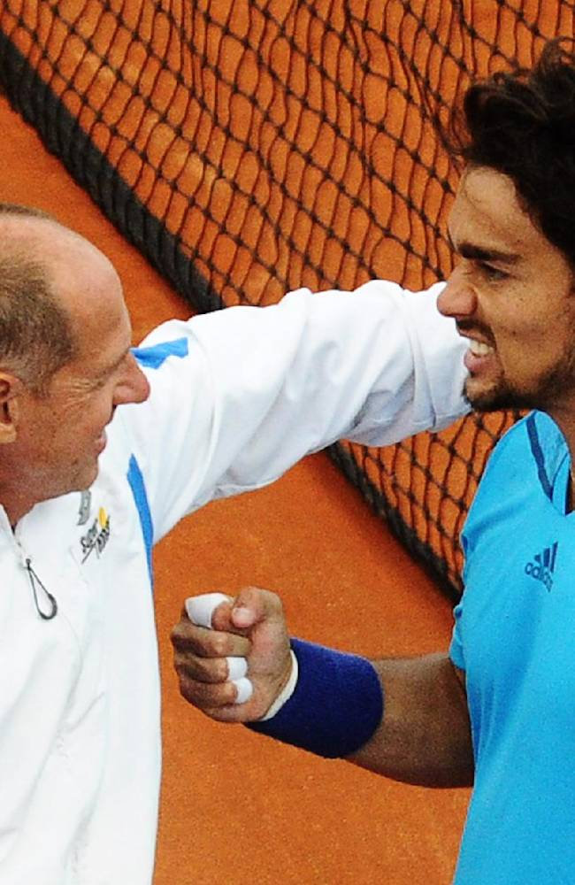 Italy's Fabio Fognini, right, celebrates with coach Corrado Barazzutti after winning a Davis Cup World Group quarterfinal match against Britain's James Ward in Naples, Italy, Friday, April 4, 2014