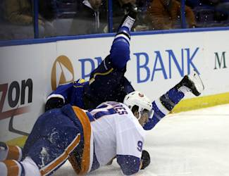 St. Louis Blues' David Backes, rear, tumbles into the boards over New York Islanders' John Tavares, front, during the first period of an NHL hockey game Thursday, Dec. 5, 2013, in St. Louis. (AP Photo/Jeff Roberson)