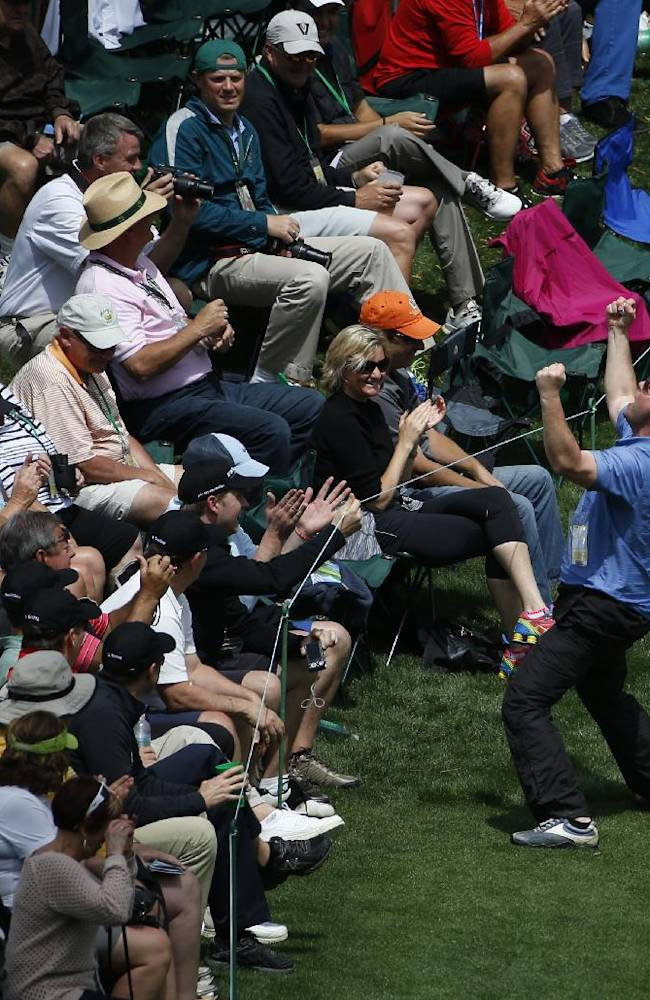 A fan reacts after being given Mike Weir, of Canada's hole-in-one ball on the 16th hole during a practice round for the Masters golf tournament Tuesday, April 8, 2014, in Augusta, Ga
