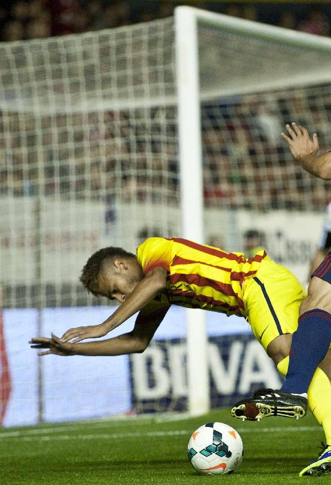 FC Barcelona's Neymar , centre,  is tackled by Osasuna's Marc Bertran, during their Spanish League soccer match, at El Sadar stadium, in Pamplona northern Spain on Saturday, Oct. 19, 2013