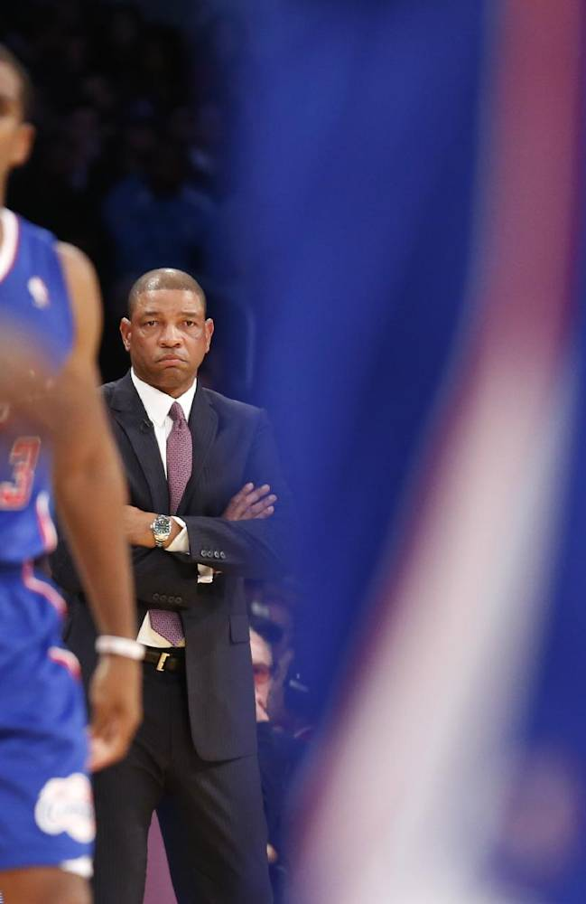 Los Angeles Clippers head coach Doc Rivers looks out as Chris Paul and other teammates take the court against the Los Angeles Lakers during a stop in play during the first half of an NBA basketball game in Los Angeles, Tuesday, Oct. 29, 2013