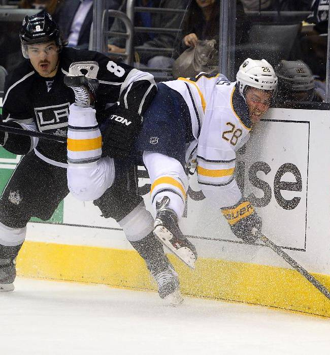 In this Nov. 7, 2013, file photo, Buffalo Sabres center Zemgus Girgensons, right, of Latvia, slams into the boards as he battles for the puck with Los Angeles Kings defenseman Drew Doughty during the first period of an NHL hockey game in Los Angeles. The photo was part of a series of images by photographer Mark J. Terrill which won the Thomas V. diLustro best portfolio award for 2013 given out by the Associated Press Sports Editors during their annual winter meeting in Indianapolis