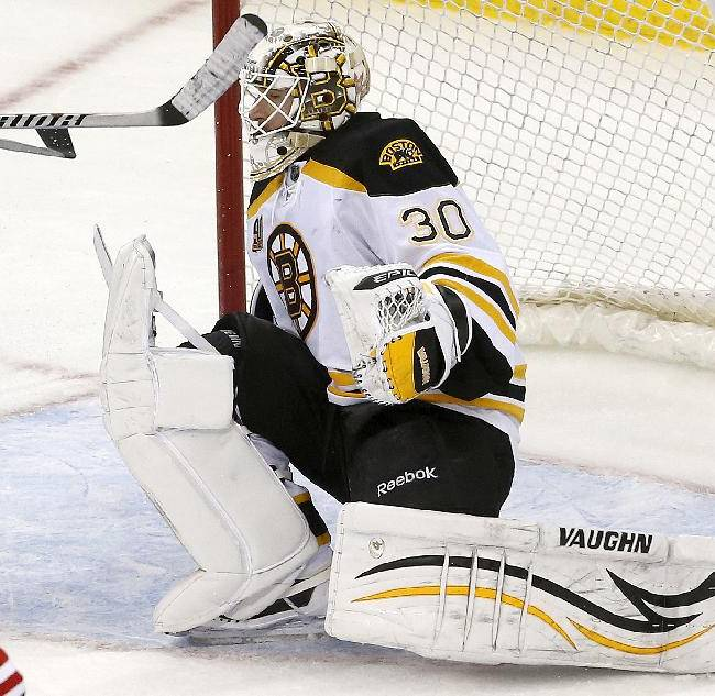 Boston Bruins goalie Chad Johnson deflects a shot by the New Jersey Devils during the third period of an NHL hockey game, Tuesday, March 18, 2014, in Newark, N.J. The Bruins won 4-2