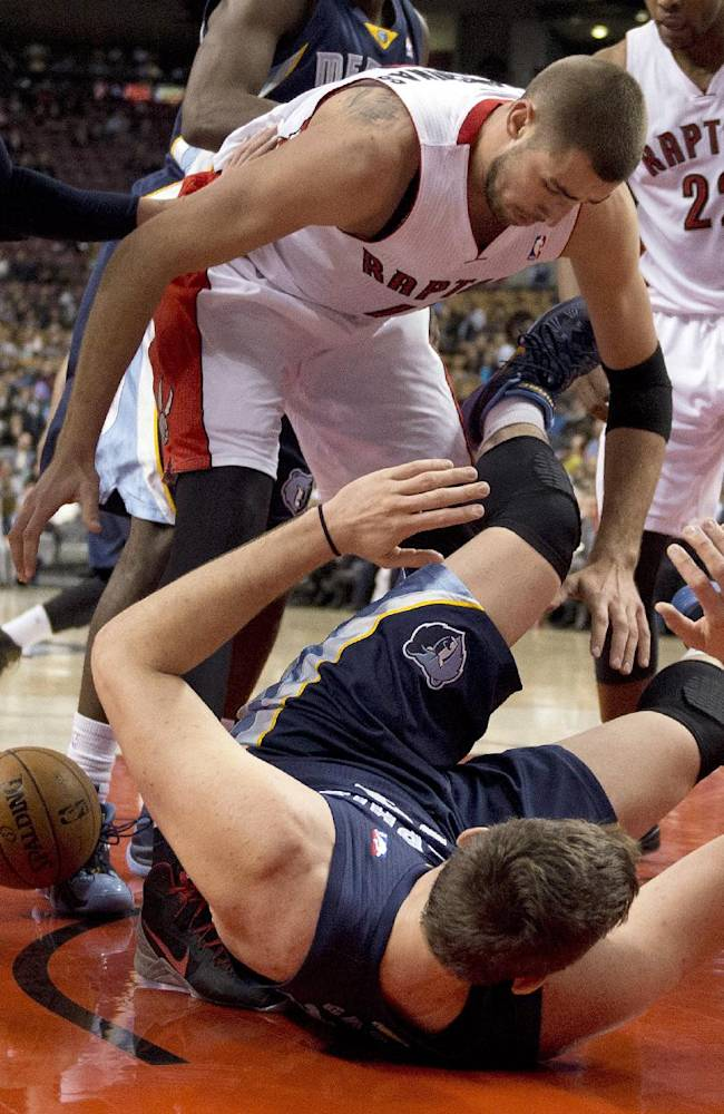 Toronto Raptors center Jonas Valanciunas, top, and Memphis Grizzlies center Marc Gasol battle for the ball during the first half of a preseason NBA basketball game in Toronto on Wednesday, Oct. 23, 2013