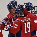 Washington Capitals left wing Alex Ovechkin (8), from Russia, celebrates with center Nicklas Backstrom (19), from Sweden, after an NHL hockey game against the Tampa Bay Lightning, Saturday, Dec. 13, 2014, in Washington. Backstrom had a hat trick, and the