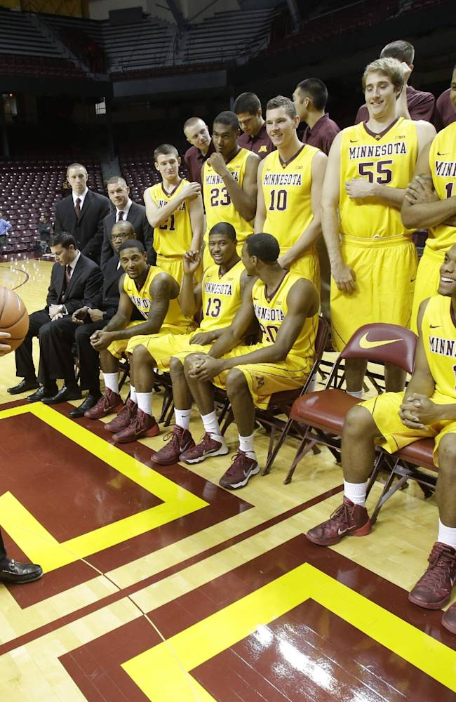 New Minnesota head basketball coach Richard Pitino, left, looks at his players before joining them for a team photo on media day, Monday, Oct. 28, 2013, in Minneapolis