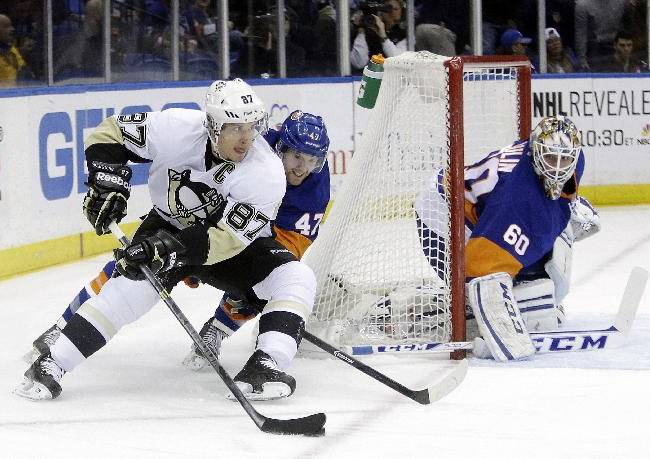 New York Islanders' Andrew MacDonald (47) defends Pittsburgh Penguins' Sidney Crosby (87) as he looks to pass away from goalie Kevin Poulin (60) during the first period of an NHL hockey game, Thursday, Jan. 23, 2014 in Uniondale, N.Y