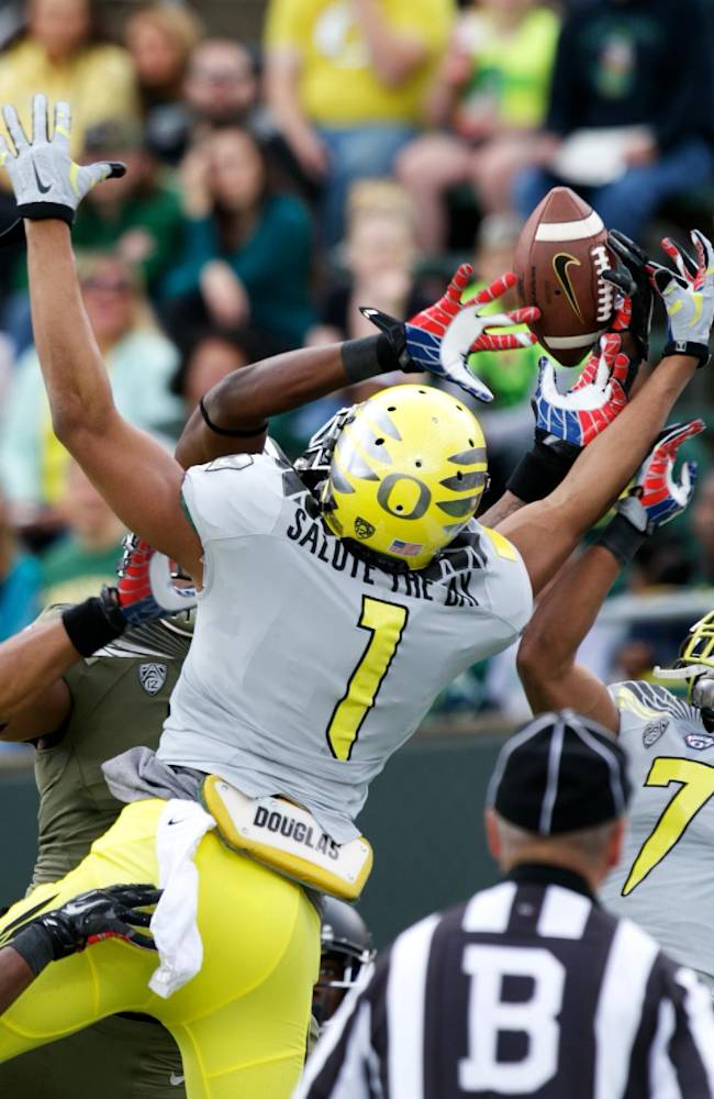 Oregon players reach for a pass during the Ducks spring NCAA college football game on Saturday, May 3, 2014, at Autzen Stadium in Eugene, Ore