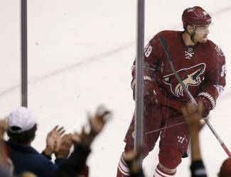 The crowd cheers as Phoenix Coyotes' Mikkel Boedker, of Denmark, skates past them after he scores a goal against the New York Islanders during the second period of an NHL hockey game Thursday, Dec. 12, 2013, in Glendale, Ariz. (AP Photo/Ross D. Franklin)