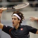 Novak Djokovic of Serbia jokingly wears a wig to impersonate former tennis player Gustavo 'Guga' Kuerten of Brazil during their exhibition match in Rio de Janeiro, Brazil, Saturday, Nov. 17, 2012. (AP Photo/Felipe Dana)