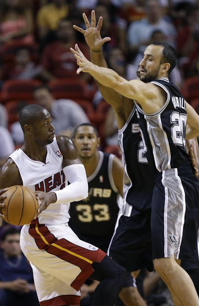 Miami Heat's Dwyane Wade (3) looks to pass as San Antonio Spurs' Manu Ginobili (20) defends during the first half of an NBA preseason basketball game, Saturday, Oct. 19, 2013, in Miami