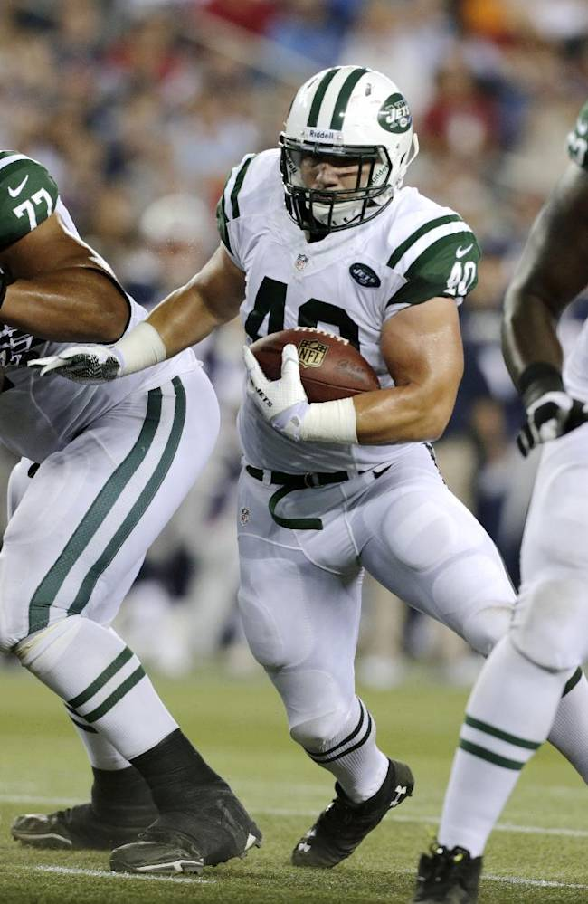 New York Jets fullback Tommy Bohanon (40) looks for running room next to New England Patriots defensive tackle Vince Wilfork (75) during the first quarter of an NFL football game Thursday, Sept. 12, 2013, in Foxborough, Mass