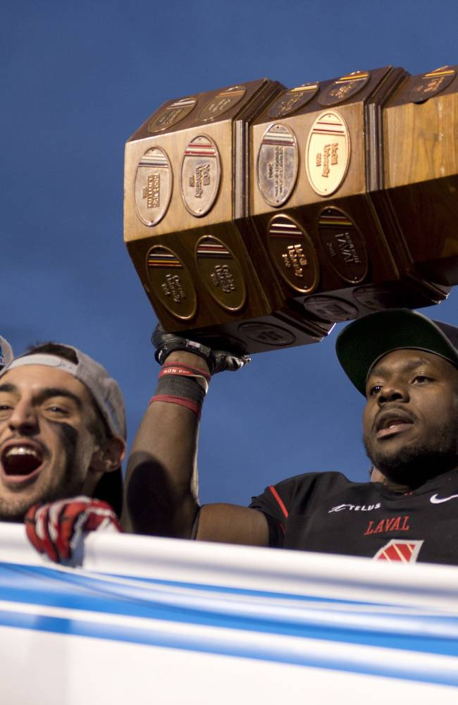 Laval Rouge et Or's Pascal Lochard, right, raises the Dunsmore Cup as teammate Vincent Plante, left, celebrates after a CIS football game against the Montreal Carabins on Saturday, Nov. 9, 2013, in Quebec City
