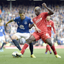 Liverpool's Mario Balotelli, right, tackles Everton's Muhamed Besic during their English Premier League soccer match at Anfield in Liverpool, England, Saturday Sept. 27, 2014.