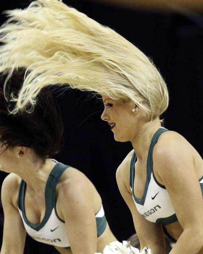 The hair flies as Oregon cheerleaders go through a routine during the second half of an NCAA college basketball game against Utah Valley in Eugene, Ore., Tuesday, Nov. 19, 2013.  Oregon won 69-54