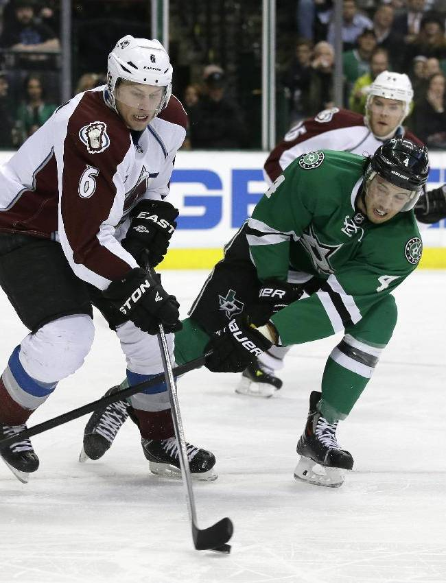 Colorado Avalanche's Erik Johnson (6) and Dallas Stars' Brenden Dillon (4) compete for control of a loose puck in the first period of an NHL hockey game, Monday, Jan. 27, 2014, in Dallas