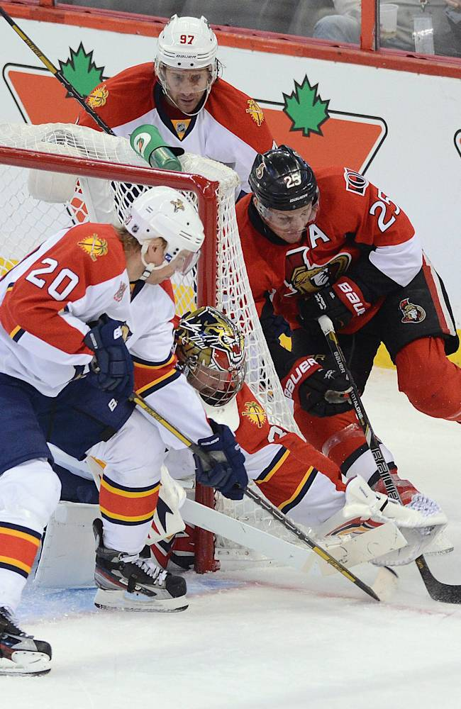 Ottawa Senators' Chris Neil, right, wraps the puck around the net as Florida Panthers' Tim Thomas reaches for hit with his glove during an NHL hockey game in Ottawa, Ontario, on Saturday, Nov. 9, 2013