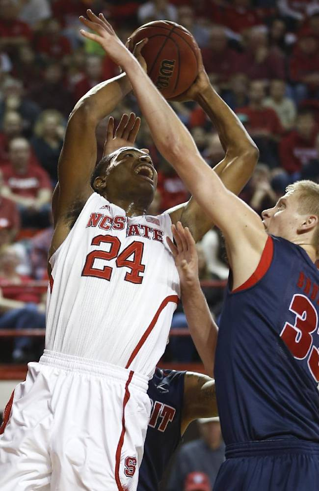 North Carolina State's T.J. Warren (24) shoots as Detroit's Evan Bruinsma (33) defends during the first half of an NCAA college basketball game at Reynolds Coliseum in Raleigh, N.C., Saturday, Dec. 14, 2013