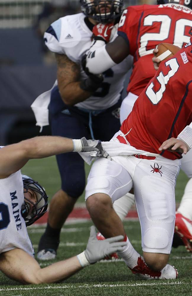 Richmond quarterback Michael Strauss (3) twists out of a sack attempt by Maine defensive lineman Michael Cole (9) during an NCAA college football game in Richmond, Va., Saturday, Sept. 28, 2013