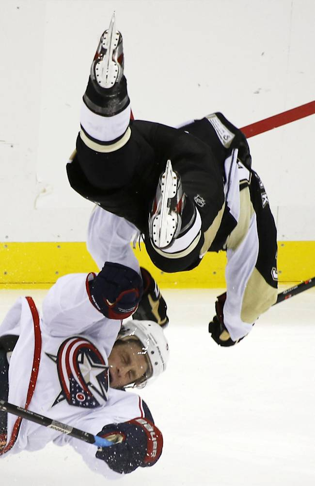 Pittsburgh Penguins' Harry Zolnierczyk (39), top, flies over Columbus Blue Jackets' Jack Skille (5) after the two collided in the first period of the NHL hockey preseason game on Saturday, Sept. 21, 2013, in Pittsburgh