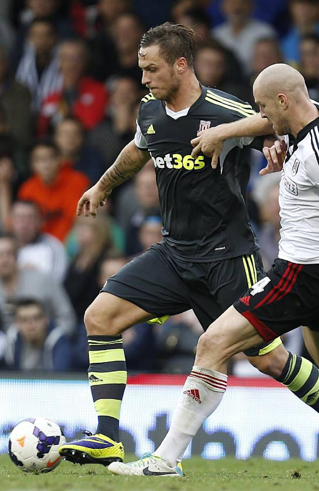 Fulham's Philippe Senderos, right, tries to stop Stoke City's Marco Arnautovic, left, during an English Premier League soccer match at the Craven Cottage ground in London, Saturday, Oct. 5, 2013. Fulham won the match 1-0