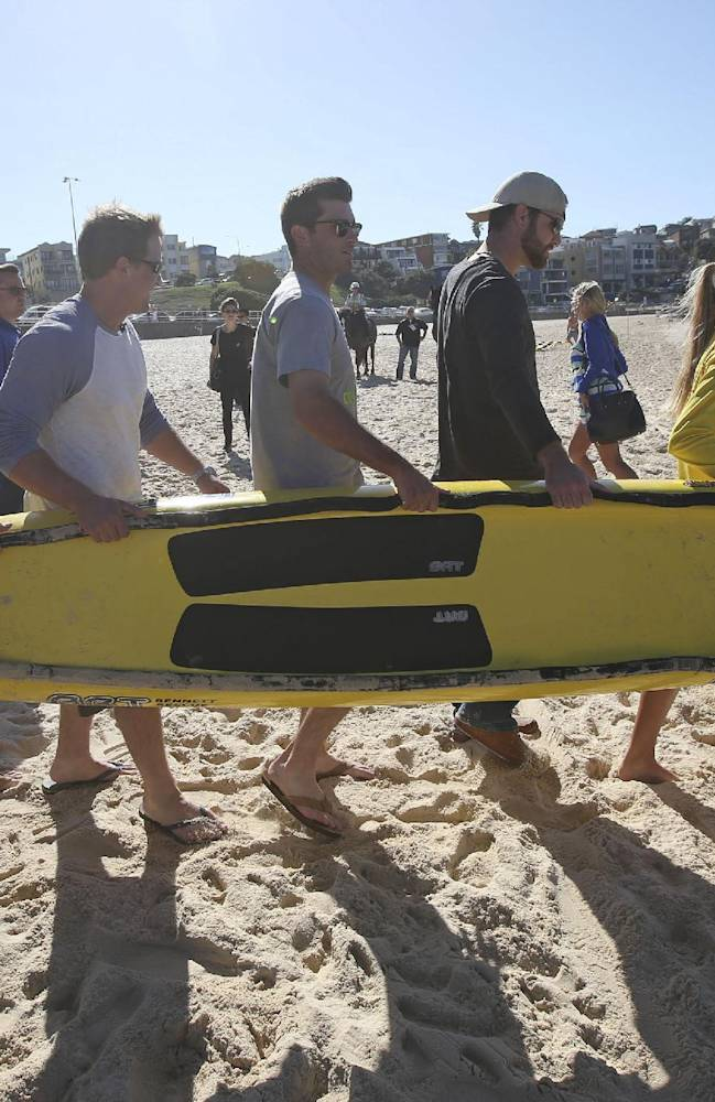 The Los Angeles Dodgers' Mike Baxter, second left, Tim Federowicz, third left, Drew Butera, third right, and Chris Withrow, help surf lifesavers Sophie Thomson and Dan Jewiss carry a rescue board down to the surf at Bondi Beach in Sydney, Wednesday, March 19, 2014. The Major League Baseball season-opening two-game series between the Los Angeles Dodgers and Arizona Diamondbacks in Sydney will be played this weekend