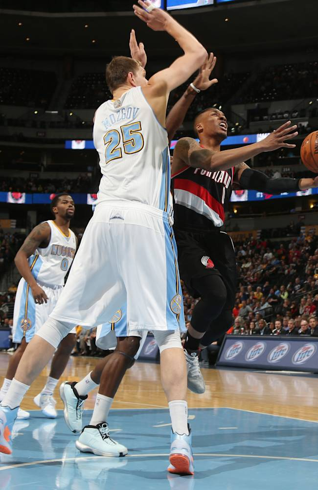 Denver Nuggets center Timofey Mozgov, left, of Russia, fouls Portland Trail Blazers guard Damian Lillard as he drives the lane for a shot in the first quarter of an NBA basketball game in Denver, Tuesday, Feb. 25, 2014