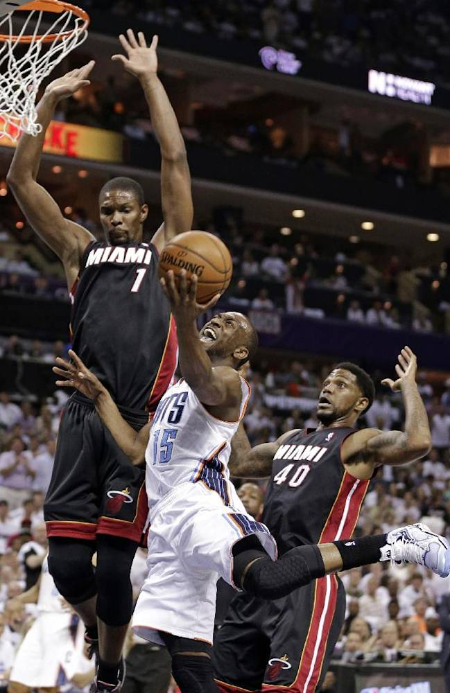 Charlotte Bobcats' Kemba Walker (15) is fouled as he drives between Miami Heat's Chris Bosh (1) and Udonis Haslem (40) during the first half in Game 3 of an opening-round NBA basketball playoff series in Charlotte, N.C., Saturday, April 26, 2014