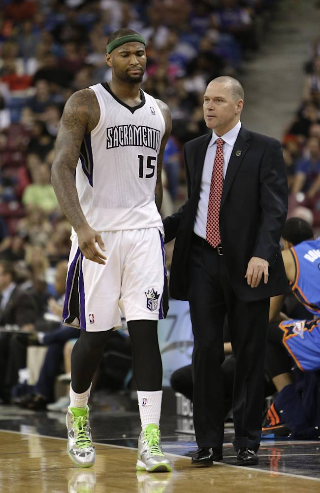 Sacramento Kings head coach Michael Malone talks with Kings center DeMarcus Cousins as he leaves the game during the closing moments of the Thunder's 107-92 win over the Kings in a NBA basketball game, Tuesday, April 8, 2014, in Sacramento, Calif