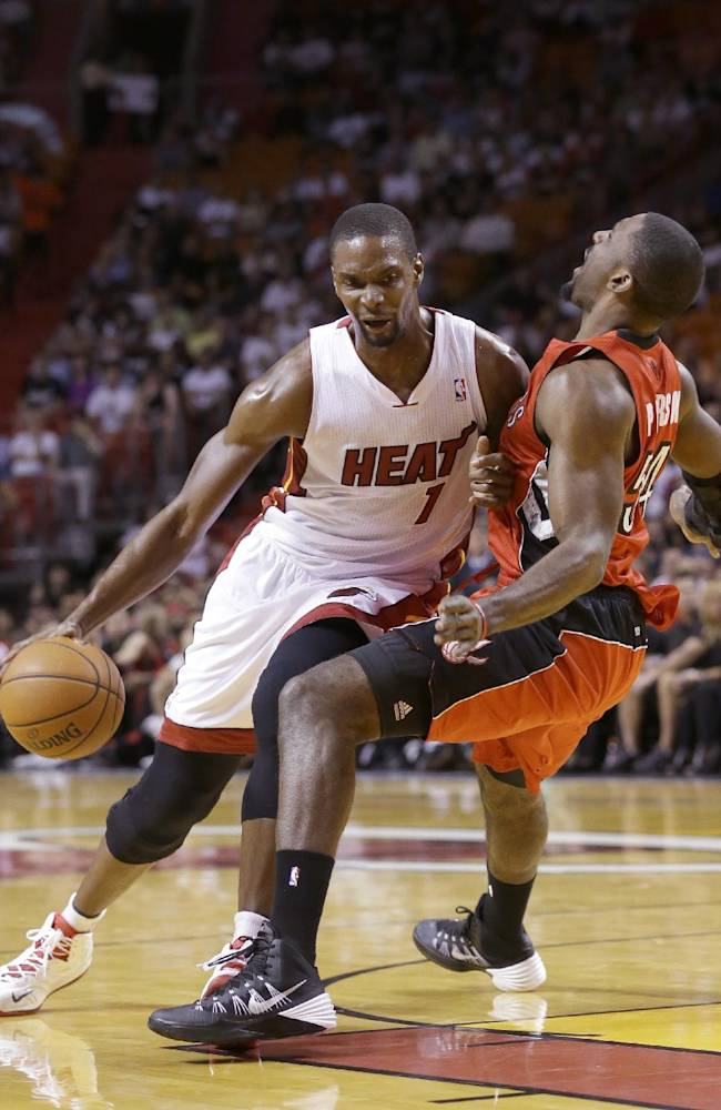 Miami Heat center Chris Bosh (1) is fouled by Toronto Raptors forward Patrick Patterson as he goes up for a shot during the first half of an NBA basketball game, Monday, March 31, 2014 in Miami