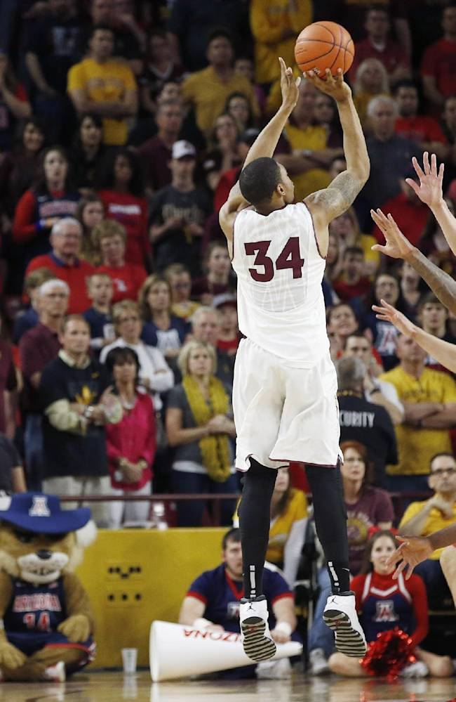 As fans look on, Arizona State's Jermaine Marshall (34) sinks a jump shot against the Arizona defense during the second overtime of an NCAA college basketball game, Friday, Feb. 14, 2014, in Tempe, Ariz.  Arizona State defeated Arizona 69-66 in double overtime