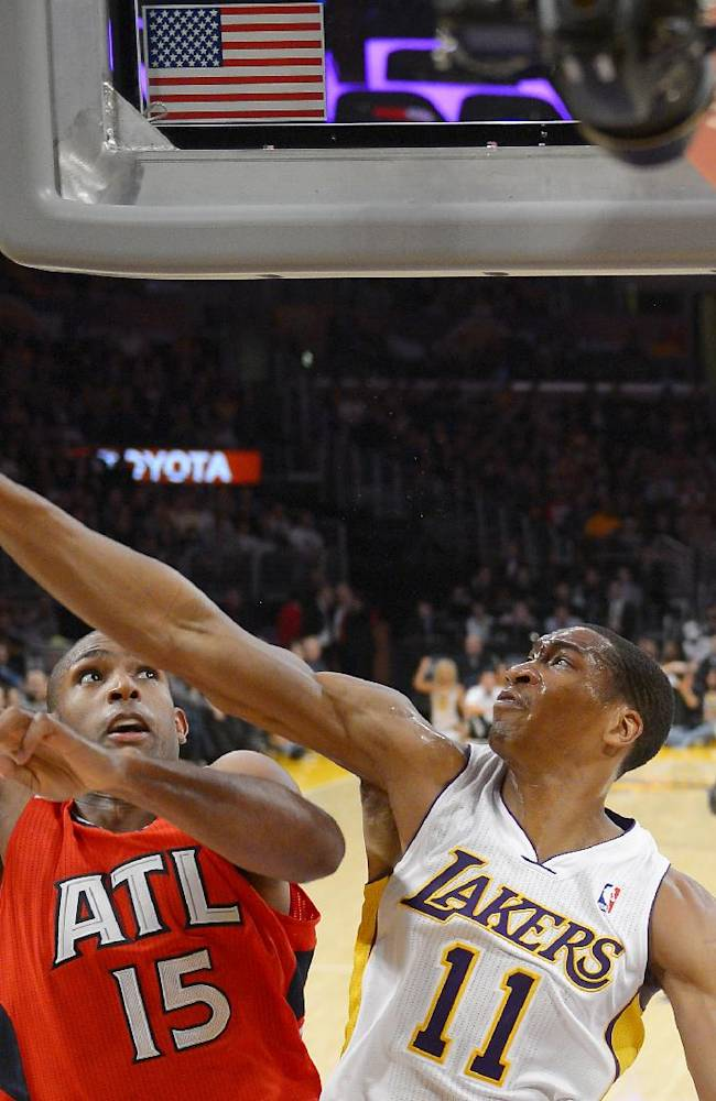 Atlanta Hawks center Al Horford, left, of the Dominican Republic, puts up a shot as Los Angeles Lakers guard Wesley Johnson defends during the first half of their NBA basketball game, Sunday, Nov. 3, 2013, in Los Angeles