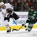 Chicago Blackhawks defenseman Brent Seabrook (7) keeps the puck away from Dallas Stars center Cody Eakin (20) in the first period of an NHL hockey game Tuesday, Dec. 10, 2013, in Dallas, Texas. (AP Photo/Sharon Ellman)