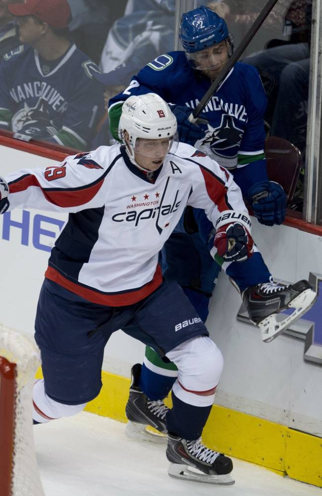 Washington Capitals center Nicklas Backstrom (19) puts Vancouver Canucks defenseman Dan Hamhuis (2) into the boards as they fight for control of the puck during the first period of NHL hockey action in Vancouver, British Columbia on Monday, Oct. 28, 2013