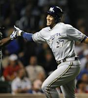 Milwaukee Brewers' Yuniesky Betancourt left, high-fives Carlos Gomez (27) after Gomez scored on a double by Jeff Bianchi against the Chicago Cubs during the ninth inning of a baseball game, Monday, July 29, 2013, in Chicago. (AP Photo/Jim Prisching)