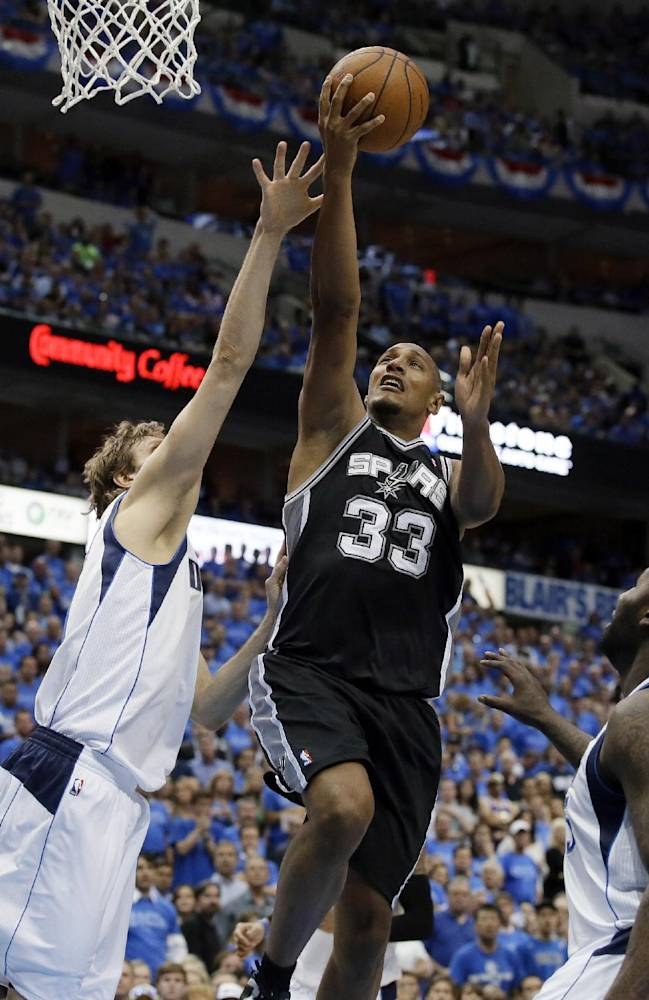Dallas Mavericks' Dirk Nowitzki, left, and DeJuan Blair, right, defend a shot by San Antonio Spurs' Boris Diaw (33) late in the second half of Game 4 of an NBA basketball first-round playoff series, Monday, April 28, 2014, in Dallas. The Spurs won 93-89