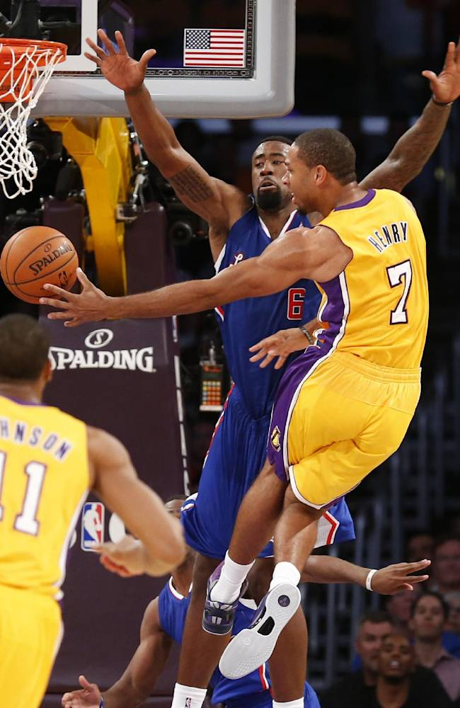 Los Angeles Lakers' Xavier Henry passes off the ball as Los Angeles Clippers' DeAndre Jordan defends him during the second half of an NBA basketball game in Los Angeles, Tuesday, Oct. 29, 2013. The Lakers won 116-103