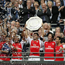 Arsenal's Mikel Arteta holds up the English FA Community Shield after his team defeated Manchester City following the traditional season opening soccer match at Wembley Stadium, London Sunday, Aug. 10, 2014. Arsenal won the game 3-0