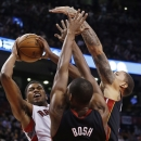 Toronto Raptors' Rudy Gay shoots against Miami Heat's Chris Bosh, center, and Michael Beasley, right, during the second half of an NBA basketball game in Toronto, Friday, Nov. 29, 2013 The Associated Press