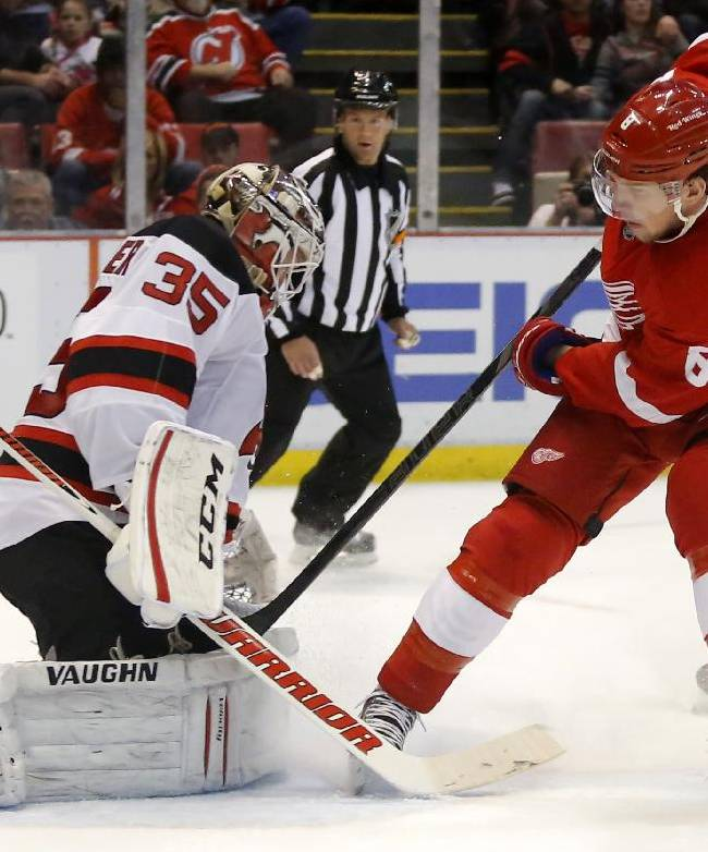 New Jersey Devils goalie Cory Schneider (35) stops a shot by Detroit Red Wings' Justin Abdelkader (8) during the second period of an NHL hockey game Friday, March 7, 2014, in Detroit