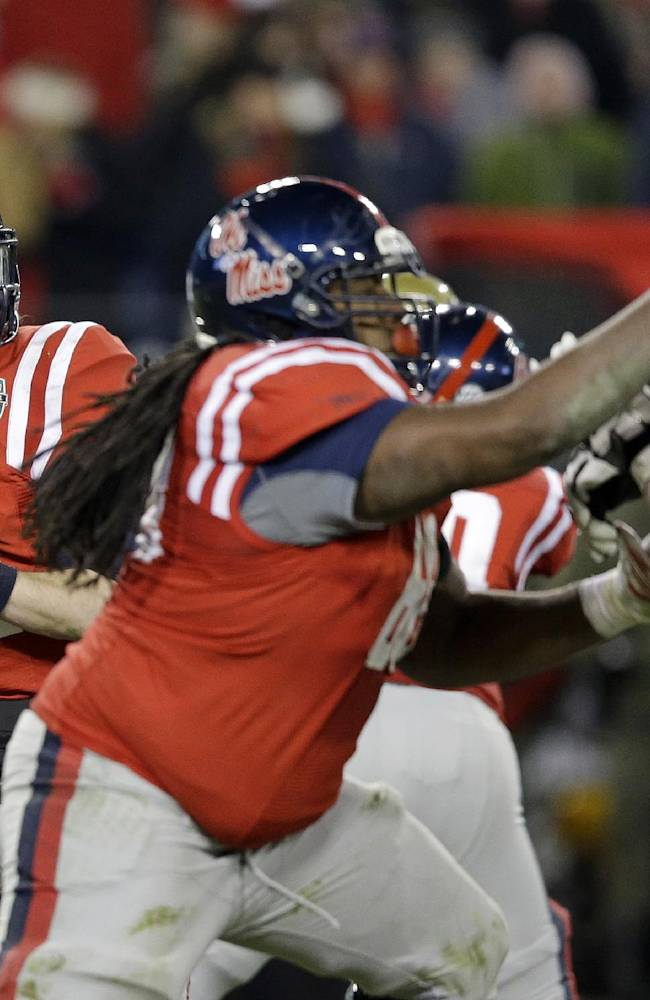 Mississippi quarterback Bo Wallace, left, drops back to pass behind the blocking of offensive linesman Justin Bell, center, in the fourth quarter of the NCAA college football Music City Bowl on Monday, Dec. 30, 2013, in Nashville, Tenn. Mississippi won 25-17